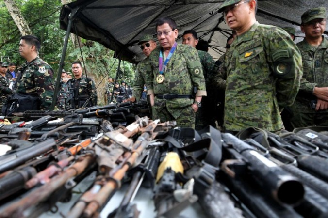 Philippine President Rodrigo Duterte inspects firearms together with Eduardo Ano, Chief of Staff of the Armed Forces of the Philippines, during his visit at the military camp in Marawi city